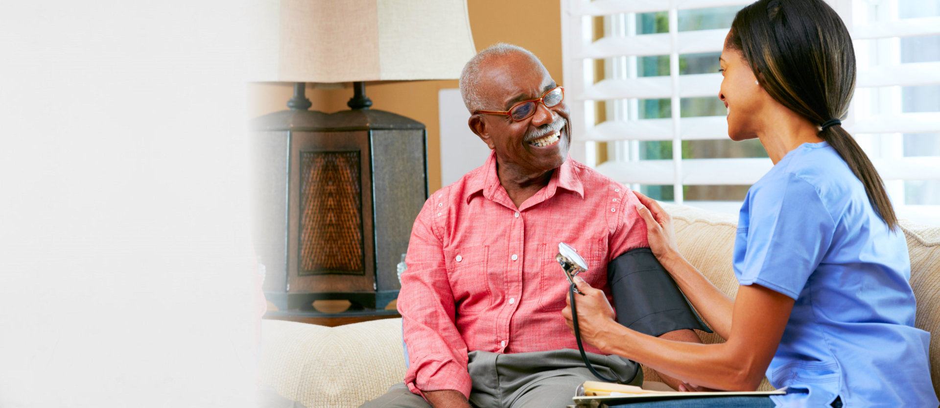 caregiver checking the blood pressure of senior man