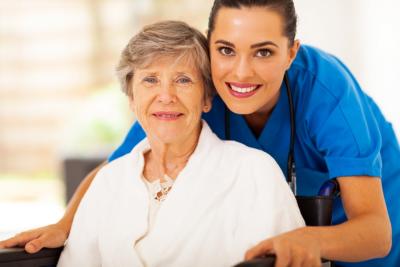 female caregiver hugging senior woman in a wheelchair